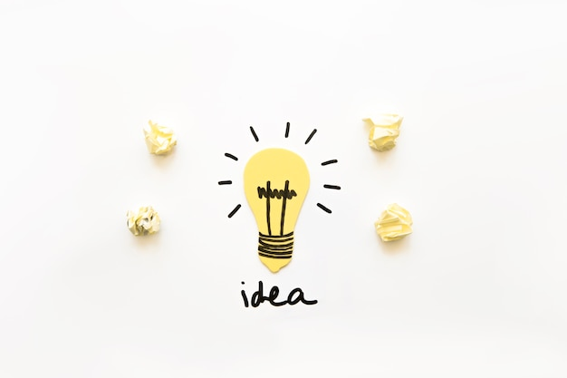 Elevated view of illuminated light bulb with idea word and crumpled paper