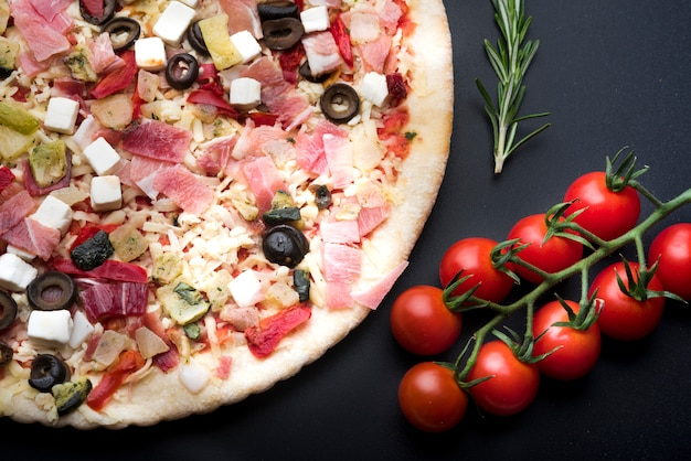 Elevated view of italian fresh pizza and ingredient on black surface