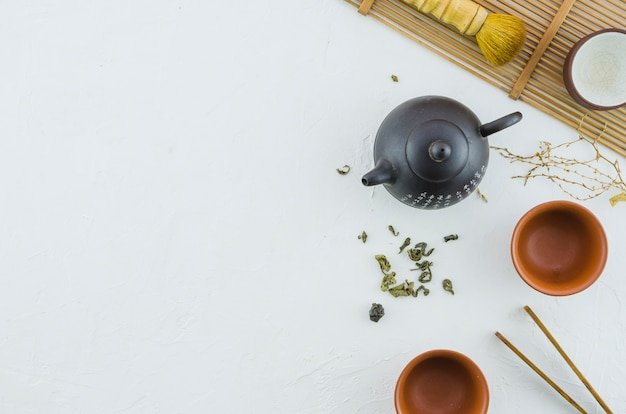 An elevated view of japanese herbal tea with tea set on white background