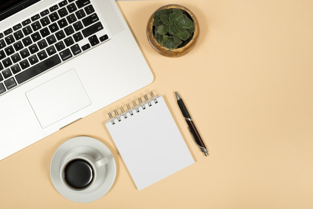 Elevated view of laptop; coffee cup; pen; and spiral notepad over beige background