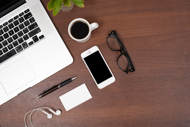 Elevated view of laptop; mobile phone; tea; earphones; pen and eye glasses on wooden table