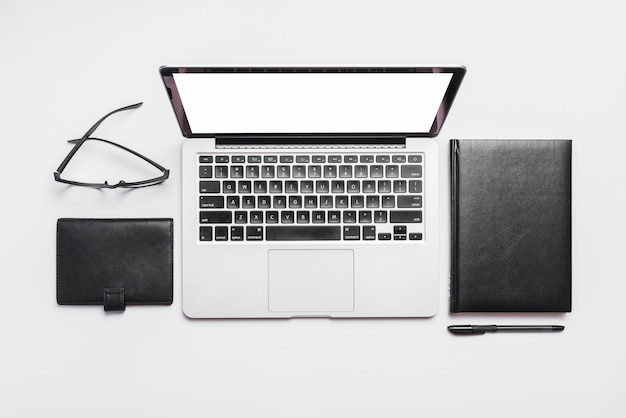 Elevated view of laptop; spectacles and diaries on white background