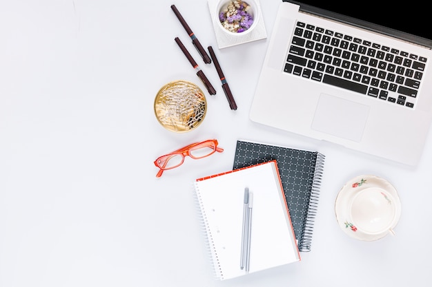 Elevated view of laptop and stationeries with an empty cup on white backdrop