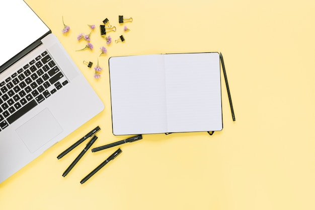 Elevated view of laptop with stationeries and flowers on yellow background