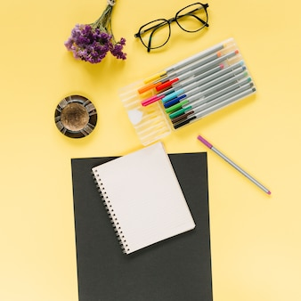 Elevated view of lavender bunch; eyeglasses; spiral notebook and felt-tip pens on dual colored background