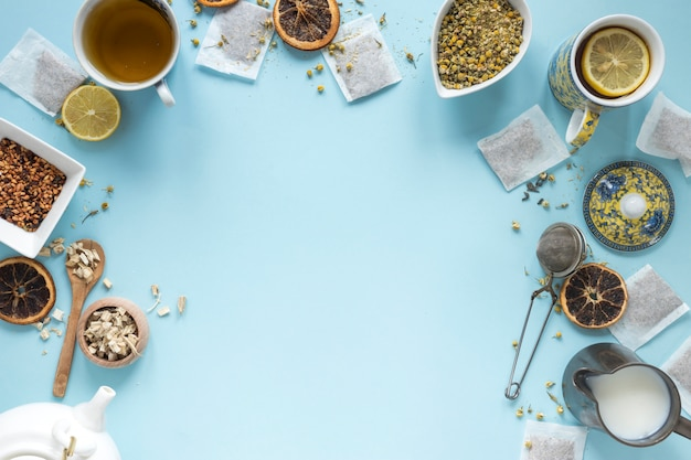 Elevated view of lemon tea; herbs; milk; strainer; dried chinese chrysanthemum flowers; teapot and teabags arranged on blue background