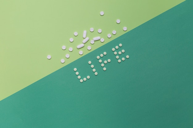 Elevated view of life word with pills on dual colored background