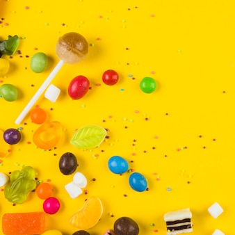 Elevated view of lollipop and candies on yellow background