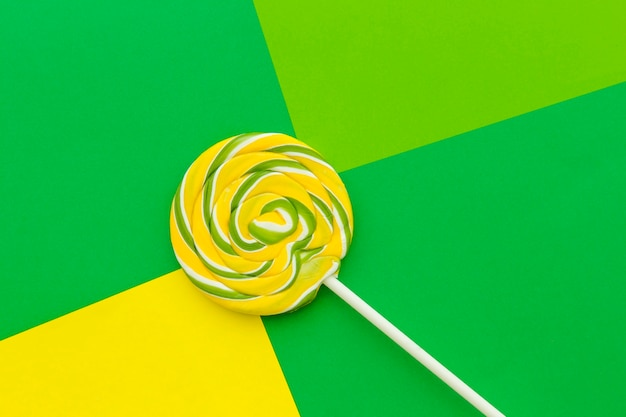 Elevated view of lollipop on colorful background