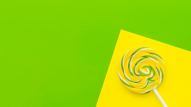Elevated view of lollipop on dual yellow and green background