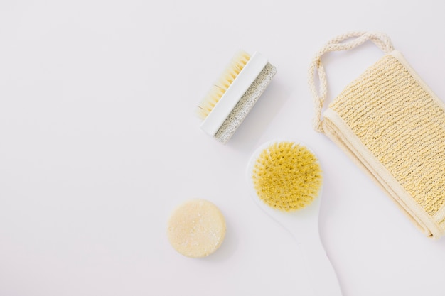 An elevated view of loofah; brush; soap and pumice stone brush on white background