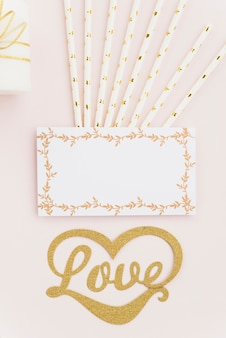 Elevated view of love text with drinking straws and blank white card on colored backdrop