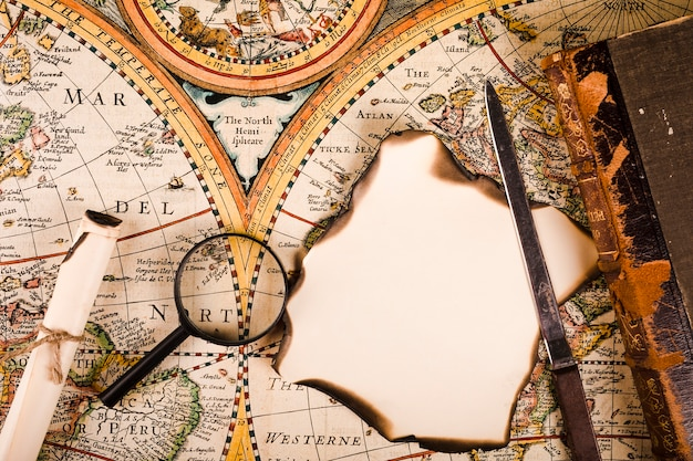 Elevated view of magnifying glass, burnt paper and knife on map