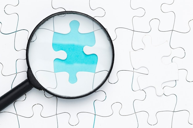 Elevated view of magnifying glass on missing puzzle piece on grid