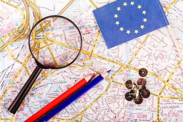 Elevated view of magnifying glass, pushpins, pencils and flag on map
