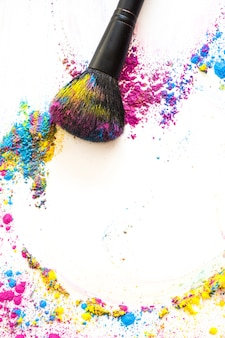 Elevated view of make up brush and colorful compact powder on white background