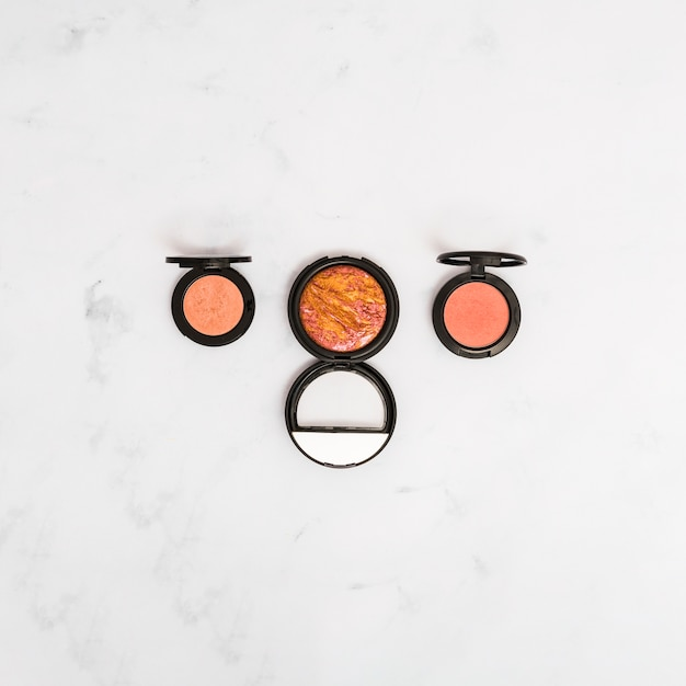 An elevated view of make-up face powder on marble textured backdrop