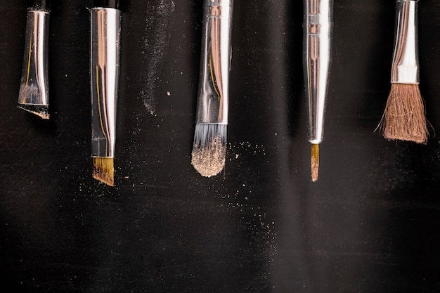 Elevated view of makeup brushes in a row on black backdrop