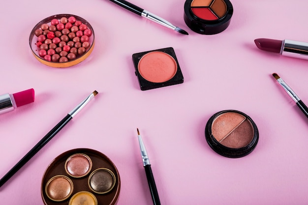 Elevated view of makeup kit with brushes on pink background