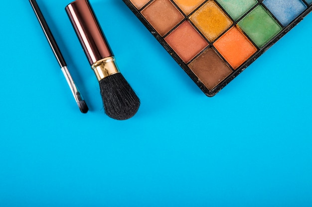 Elevated view of makeup palette and brushes on blue background