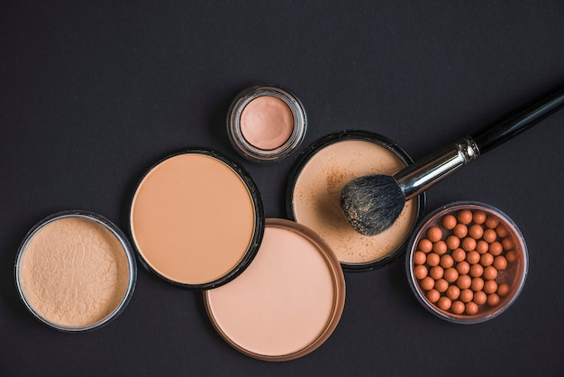 Elevated view of makeup products and brush on black surface