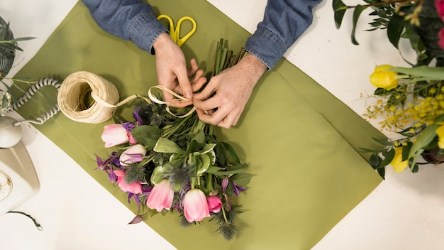 An elevated view of male tourist tying the flower bouquet with string on green paper over the desk