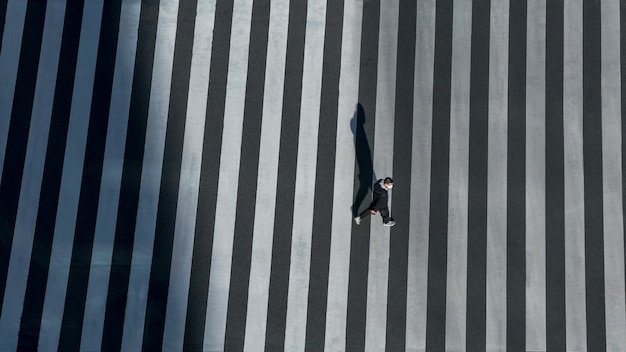 Elevated view over a man on pedestrian crossing in road intersection of japan. aerial view of people at crosswalk. asia downtown. metropolitan tokyo city