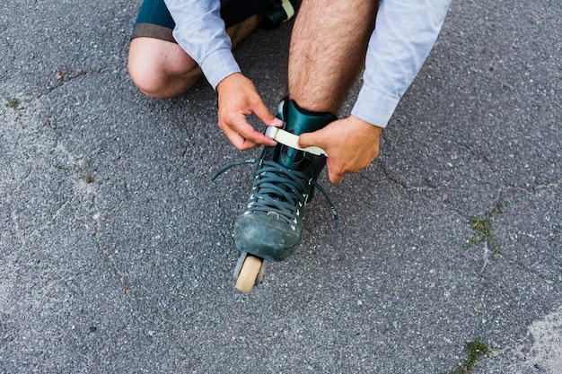 Elevated view of a man's hand putting on rollerskate
