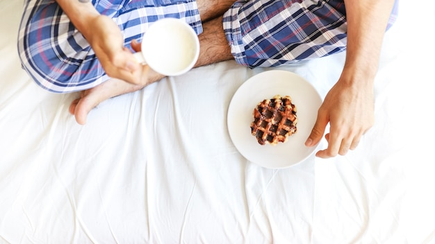 Elevated view of a man sitting on bed having breakfast
