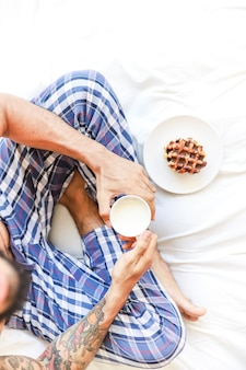 Elevated view of man with cup of milk and waffle sitting on bed