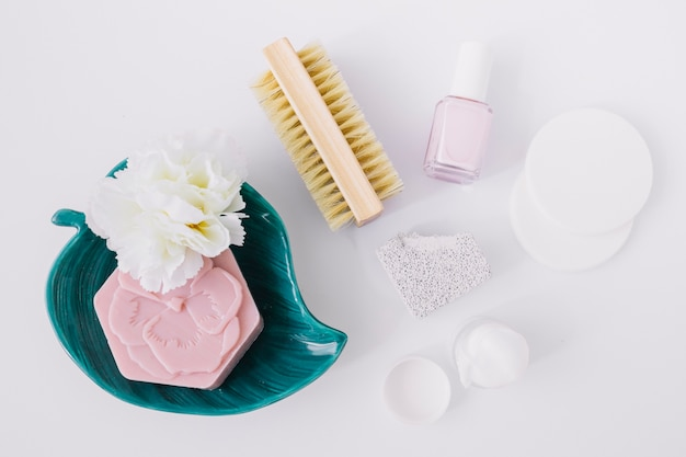 Elevated view of manicure products with pink soap bar on white surface