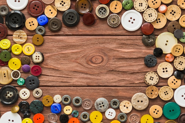 Elevated view of many buttons forming circle on wooden plank