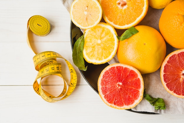 Elevated view of measuring tape and citrus fruits on plate