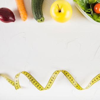Elevated view of measuring tape and healthy food on white background