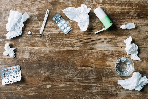 Elevated view of medicines; crumpled tissue paper; thermometer; throat spray and glass of water on wooden backdrop