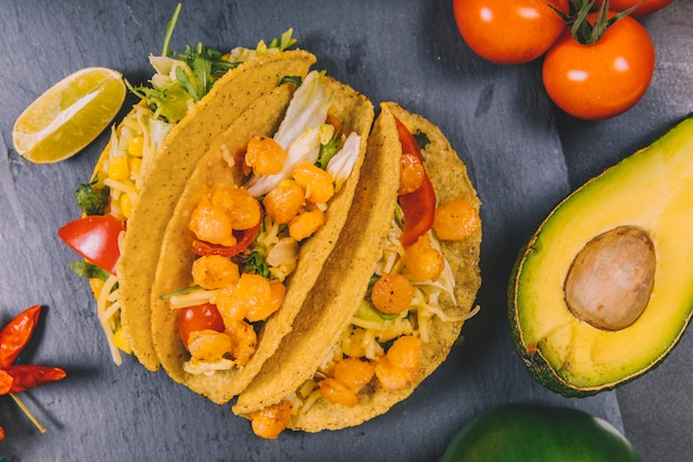 Elevated view of mexican corn tacos with vegetables and avocado on black slate