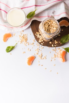 An elevated view of milk; basil leaves; oats; orange slices and napkin over white background