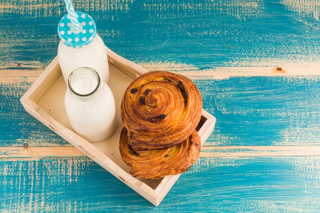 Elevated view of milk bottles and sweet french pastries in wooden tray over blue table