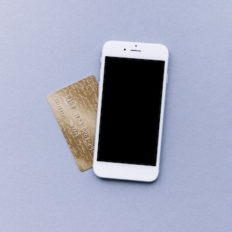 Elevated view of mobile phone and credit card on grey background