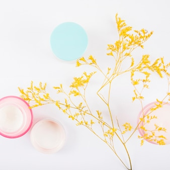 Elevated view of moisturizing creams and yellow flowers on white backdrop