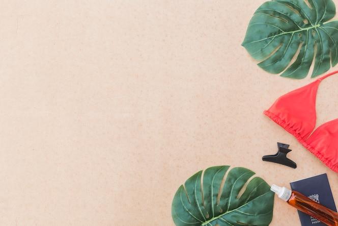 Elevated view of monstera leaf, bikini, hairclip and perfume