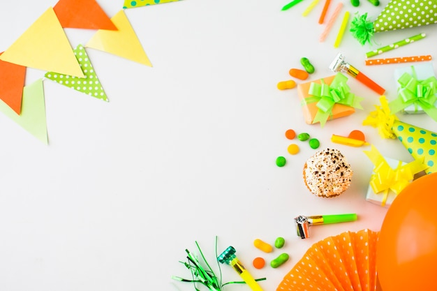 Elevated view of muffins; gift box; candies and party accessories on white backdrop
