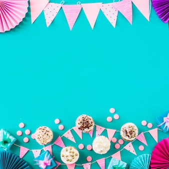 Elevated view of muffins with party accessories on green backdrop