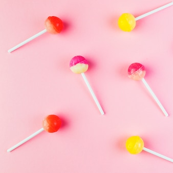 Elevated view of multi colored lollipops on pink backdrop