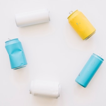 Elevated view of multi colored tin cans over white background