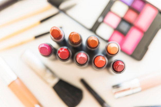 Elevated view of multicolored lipstick shades with palette of cosmetic eye shadow and cosmetics
