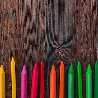 Elevated view of multicolored wax crayons on brown plank