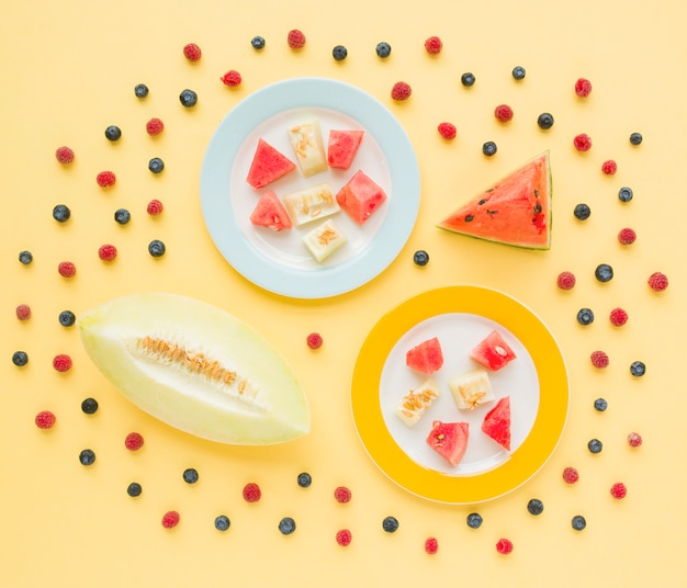 An elevated view of muskmelon and watermelon slices decorated with blueberries and raspberries on yellow backdrop