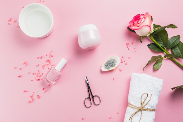 Elevated view of nail varnish; scissors; salt; towel; flowers and moisturizing cream on pink surface