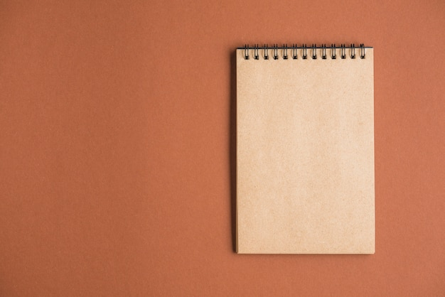 Elevated view of notepad on colored background